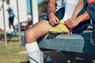 Buy stock photo Shot of a rugby player tying his shoelaces while sitting on a bench
