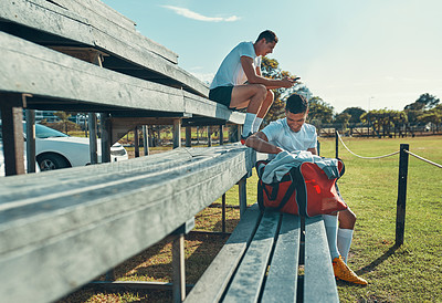 Buy stock photo Shot of two rugby players sitting on a bench