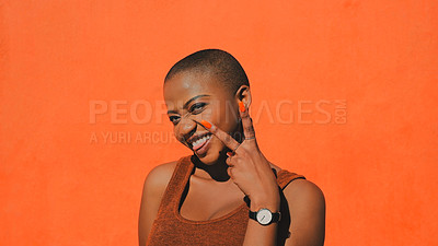 Buy stock photo Shot of an attractive young woman making a peace gesture against an orange wall outdoors