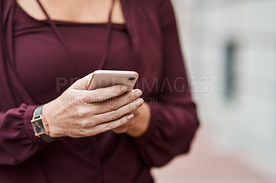 Buy stock photo Cropped shot of an unrecognisable businesswoman using a smartphone against an urban background