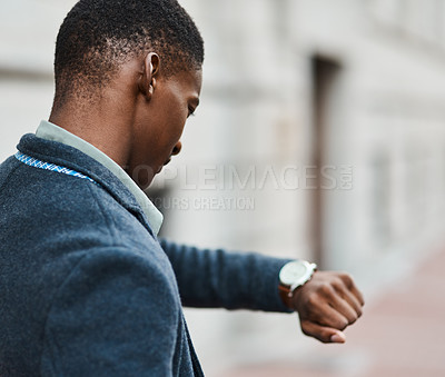 Buy stock photo Shot of a young businessman checking the time against an urban background