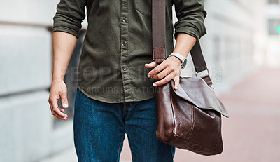 Buy stock photo Cropped shot of an unrecognisable businessman walking through the city