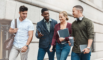 Buy stock photo Shot of a group of businesspeople using a smartphone together while walking through the city