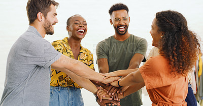 Buy stock photo Shot of a group of young businesspeople joining hands in solidarity in a modern office
