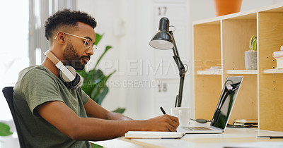 Buy stock photo Shot of a young businessman writing in a notebook at his desk in a modern office