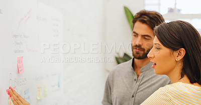 Buy stock photo Shot of a young businessman and businesswoman using a digital tablet during a brainstorming session in a modern office