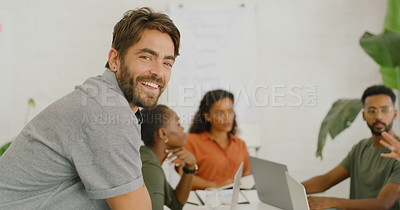 Buy stock photo Shot of a confident young businessman having a meeting with his colleagues in a modern office
