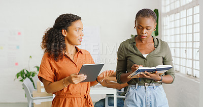 Buy stock photo Shot of two young businesswomen using a digital tablet and making notes during a discussion in a modern office