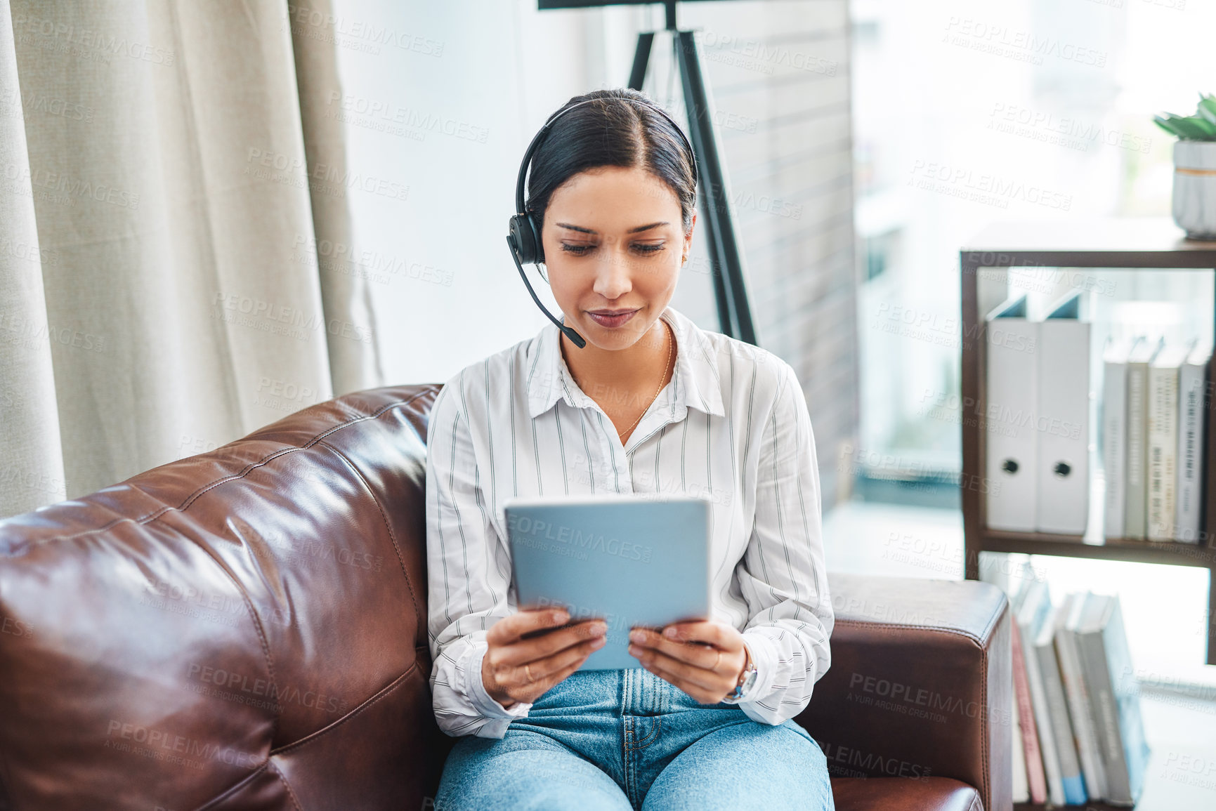 Buy stock photo Shot of a young woman using a digital tablet and headset while working from home