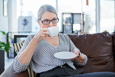 Buy stock photo Shot of a mature businesswoman drinking tea in an office lounge