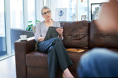 Buy stock photo Shot of a mature businesswoman using a digital tablet while having a discussion with a colleague in an office