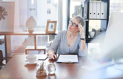 Buy stock photo Shot of a mature businesswoman going through paperwork in an office