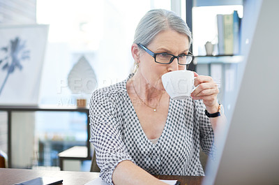 Buy stock photo Shot of a mature businesswoman drinking tea while working on a computer in an office