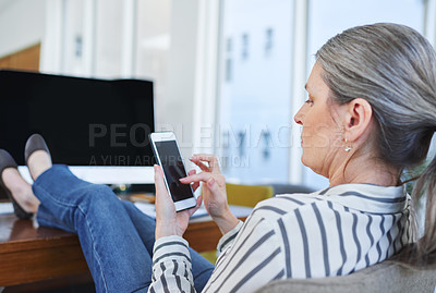 Buy stock photo Rearview shot of a mature businesswoman using a cellphone while sitting with her feet up on a desk in an office