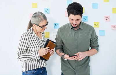 Buy stock photo Shot of two businesspeople using a cellphone together in an office