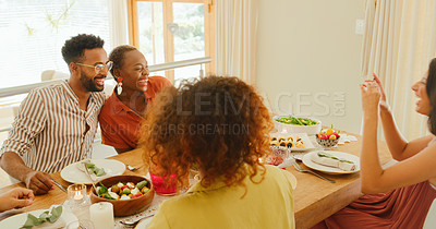 Buy stock photo Shot of a young woman taking pictures of her friends during a lunch party at home