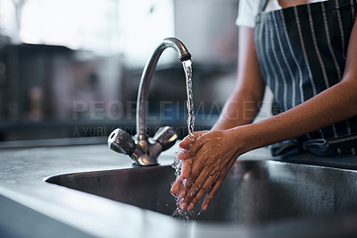 Buy stock photo Cropped shot of a  woman washing her hands in the sink of a commercial kitchen