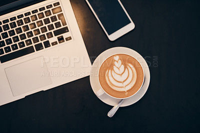 Buy stock photo Shot of a laptop, coffee and smartphone on a table in a cafe