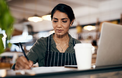 Buy stock photo Shot of a young woman using a laptop and going over paperwork while working in a cafe