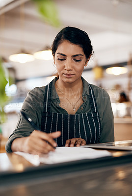 Buy stock photo Shot of a young woman going over paperwork while working in a cafe