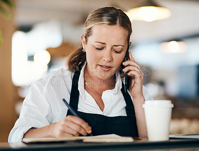 Buy stock photo Shot of a mature woman using a laptop and smartphone while working in a cafe