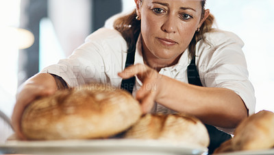 Buy stock photo Shot of a mature woman putting a selection of freshly baked breads on display in her bakery