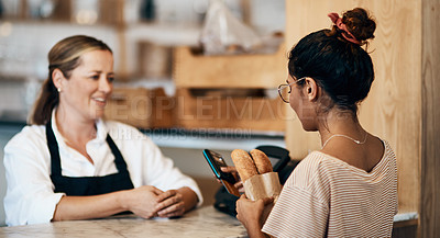 Buy stock photo Shot of a young woman paying with for freshly made baguettes at a bakery