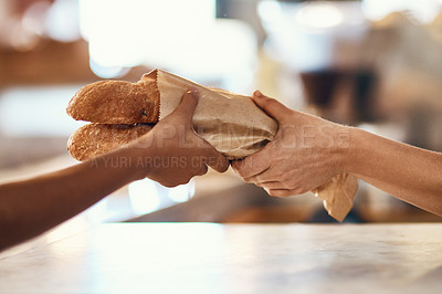 Buy stock photo Cropped shot of a woman buying freshly made baguettes at a bakery