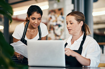 Buy stock photo Shot of two women using a laptop together while working in a cafe