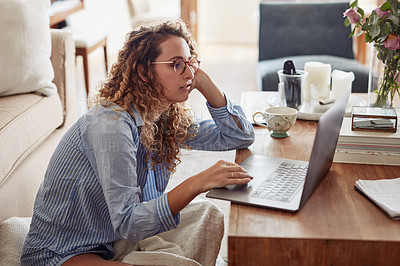 Buy stock photo Shot of a young woman using a laptop and looking bored while working at home