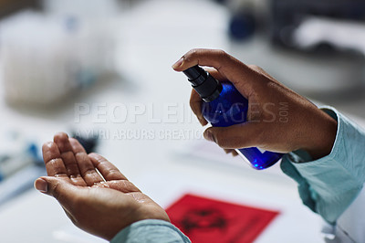 Buy stock photo Cropped shot of an unrecognizable female scientist sanitizing her hands regularly while working in the laboratory