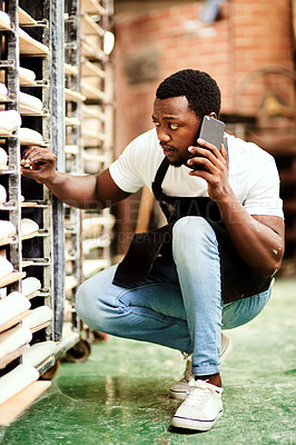 Buy stock photo Shot of a male baker talking on the phone while busy checking a baking trolley