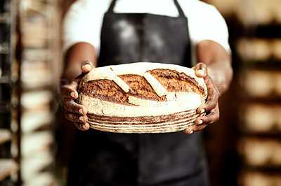 Buy stock photo Cropped shot of a male baker holding a freshly baked loaf of bread in his hands