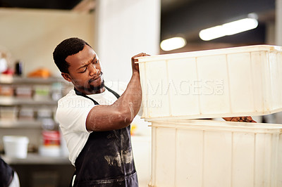 Buy stock photo Cropped shot of a young man working in a bakery