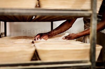 Buy stock photo Cropped shot of a male baker placing dough on a baking trolley