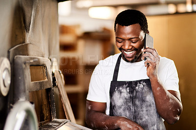 Buy stock photo Cropped shot of a male baker using his cellphone while working