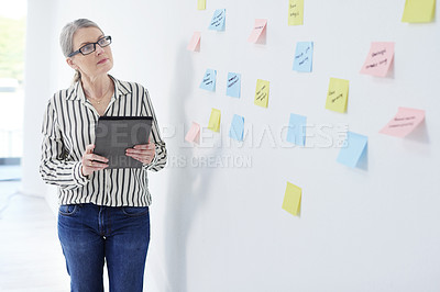 Buy stock photo Shot of a mature businesswoman using a digital tablet while brainstorming with notes on a wall in an office