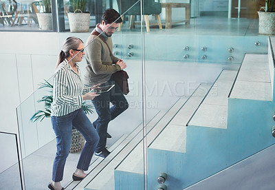 Buy stock photo Shot of two businesspeople using a digital tablet together while walking up a staircase in an office