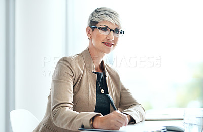 Buy stock photo Shot of a young businesswoman looking thoughtful while writing notes in an office