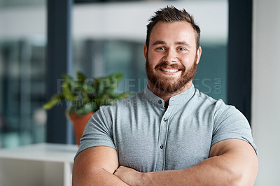 Buy stock photo Portrait of a young businessman standing with his arms crossed in an office