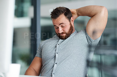Buy stock photo Shot of a young businessman scratching his head while working in an office