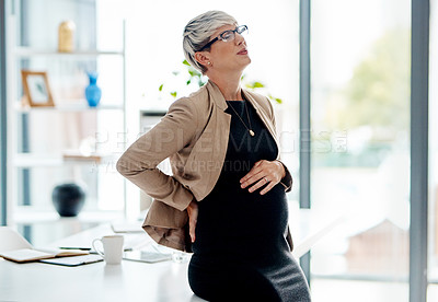 Buy stock photo Shot of a pregnant businesswoman suffering with pain in an office