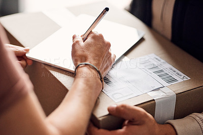 Buy stock photo Closeup shot of an unrecognisable woman using a digital tablet to sign for a delivery from the courier