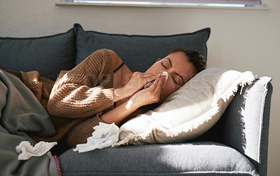 Buy stock photo Shot of an attractive young woman blowing her nose while resting on the sofa at home