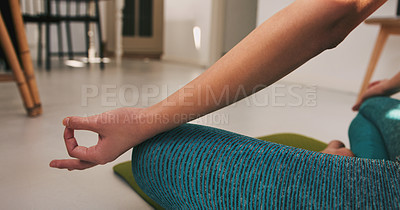 Buy stock photo Closeup shot of an unrecognisable woman meditating while practising yoga at home