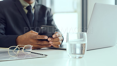 Buy stock photo Cropped shot of an unrecognisable businessman using a smartphone and laptop at his desk in a modern office