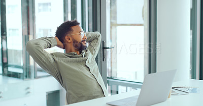 Buy stock photo Shot of a young businessman taking a break at his desk in a modern office