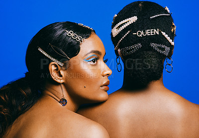 Buy stock photo Cropped shot of two beautiful young women posing with hair accessories against a blue background