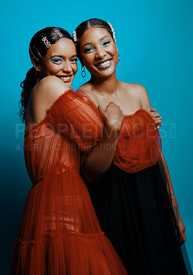 Buy stock photo Shot of two beautiful young women wearing mesh dresses while posing against a blue background