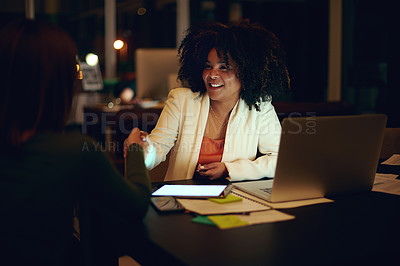 Buy stock photo Shot of two businesswomen shaking hands in an office at night